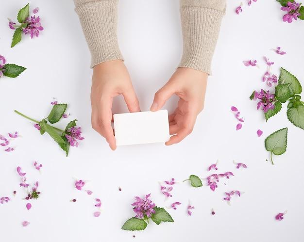 Mãos femininas segurar um cartão de visita retangular em branco sobre uma superfície branca com flores cor de rosa Foto Premium