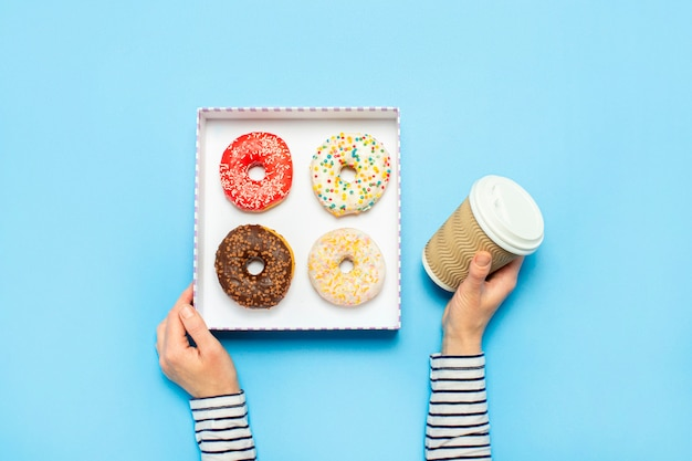 Mãos femininas segurar uma caixa com donuts, uma xícara de café em um azul. loja de confeitaria conceito, bolos, café. Foto Premium