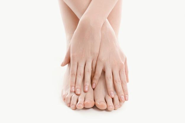 Mãos femininas sobre os pés, conceito de cuidados da pele Foto gratuita