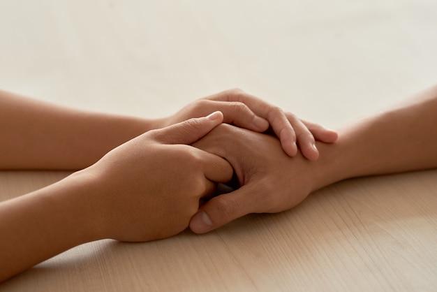 Mãos femininas tocando as mãos masculinas, tranquilizando o namorado Foto gratuita