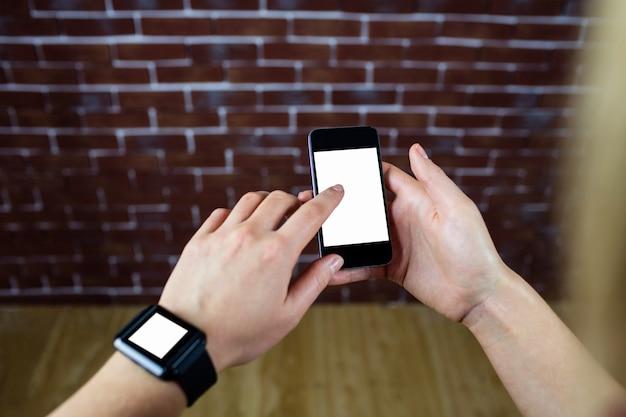 Mãos femininas usando smartphone e relógio inteligente Foto Premium