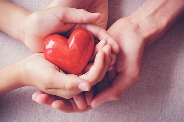 Mãos holiding coração vermelho, conceito de família de cuidados de saúde Foto Premium