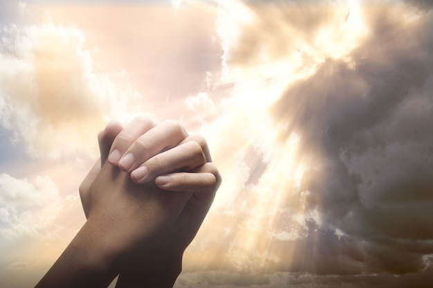 Mãos humanas levantadas enquanto orava a deus com um céu dramático Foto Premium