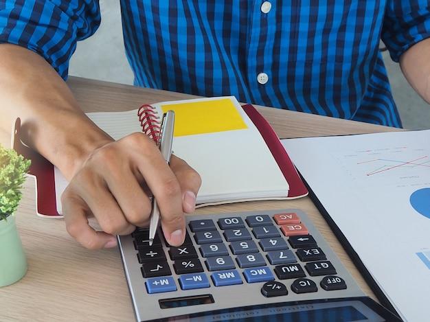 Mãos humanas usando uma calculadora Foto Premium