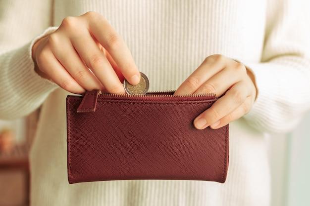 Mãos, introduzindo uma moeda em uma carteira Foto Premium