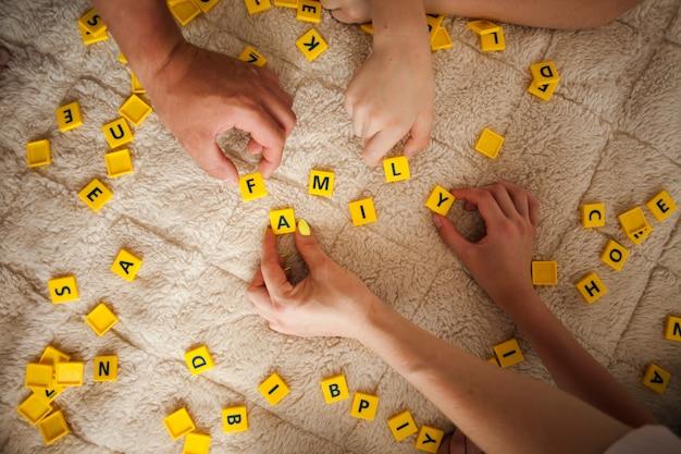 Mãos jogando jogo de scrabble no tapete em casa Foto gratuita