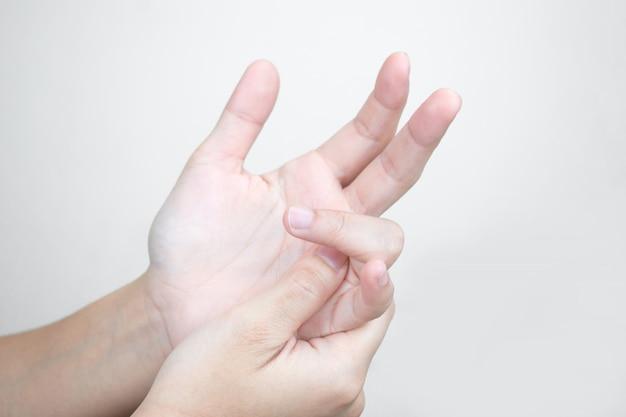 Mãos jovens têm dor nas mãos e massagem nos dedos doloridos. conceito de cuidados de saúde Foto Premium