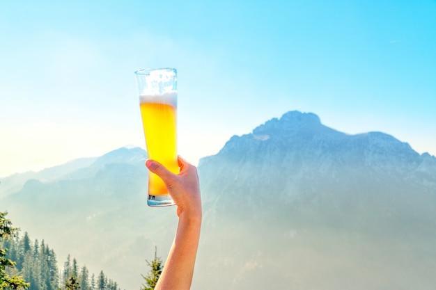Mãos, levantando o vidro de chope e feliz aproveitando o tempo de colheita no exterior na cena bela montanha Foto Premium