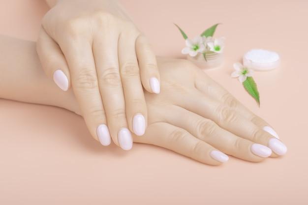 Mãos lindas com flores silvestres em cima da mesa, cosméticos anti-envelhecimento e anti-rugas para as mãos. cuidados com a pele e beleza, hidratação da pele e spa Foto Premium