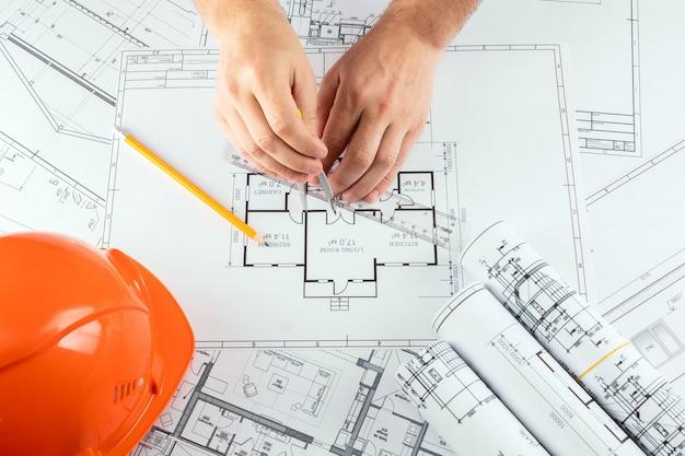 Mãos masculinas, capacete alaranjado, lápis, desenhos de construção arquitectónicos, fita métrica. Foto Premium