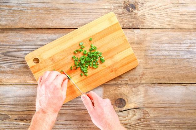 Mãos masculinas cortam uma cebola verde em uma placa de corte Foto Premium