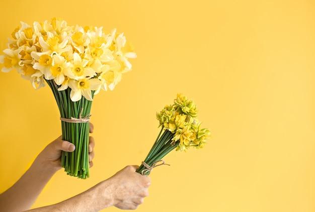 Mãos masculinas de fundo com um buquê de flores. Foto gratuita