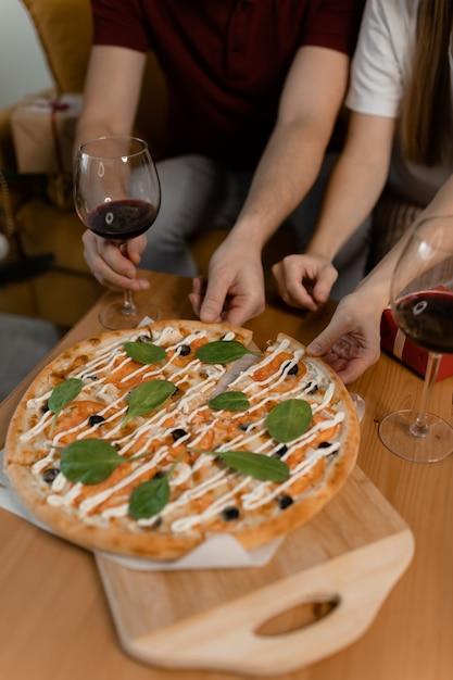 Mãos masculinas e femininas pegam pizza da mesa. há vinho na mesa. data do dia dos namorados Foto Premium