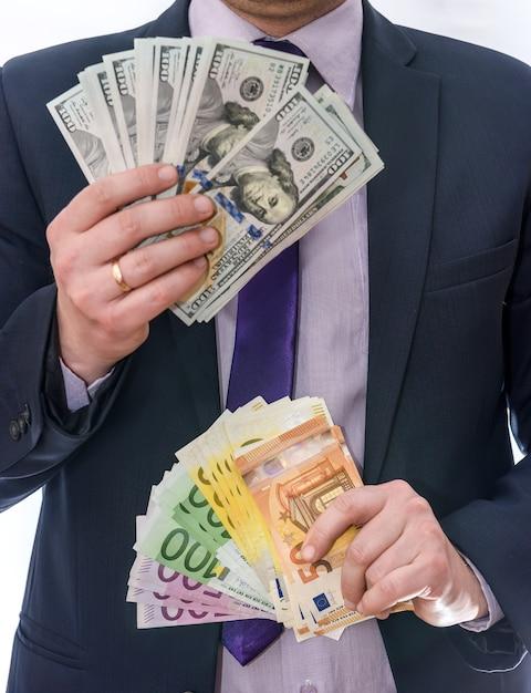 Mãos masculinas segurando notas de dólar e euro em leque Foto Premium