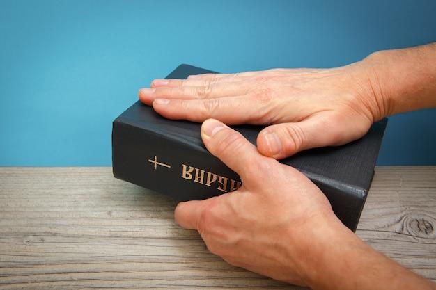 Mãos masculinas segurando uma bíblia apoiada em uma mesa de madeira título do livro tradução da bíblia holly Foto Premium