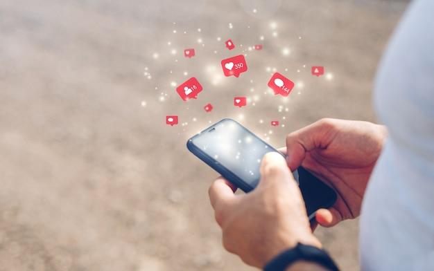 Mãos masculinas usando smartphone móvel com mídia social de ícone e rede social. conceito de marketing. Foto Premium