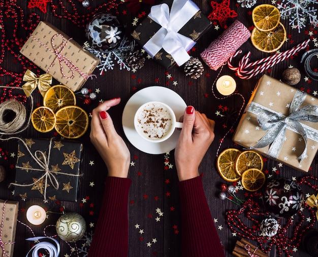 Mãos mulher, segurando, copo café, bebida, natal, feriado, caixa presente, decorado, festivo, tabela Foto gratuita