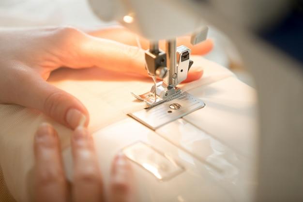 Mãos na máquina de costura Foto gratuita