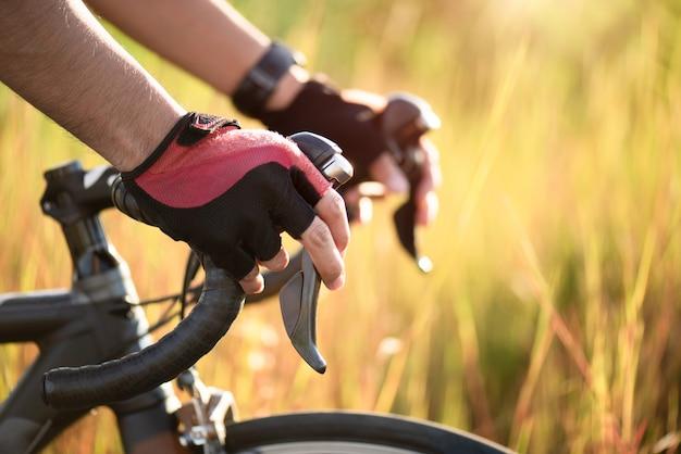 Mãos nas luvas que seguram o guiador da bicicleta da estrada. esportes e conceito ao ar livre. Foto Premium