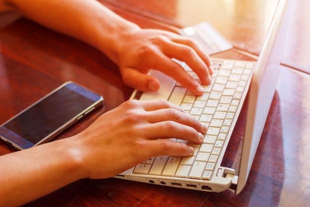 Mãos no teclado e telefone com cartão de crédito, deitado na mesa, conceito do negócio Foto Premium