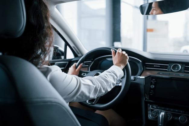Mãos no volante. linda empresária testando seu novo carro no salão automóvel Foto gratuita