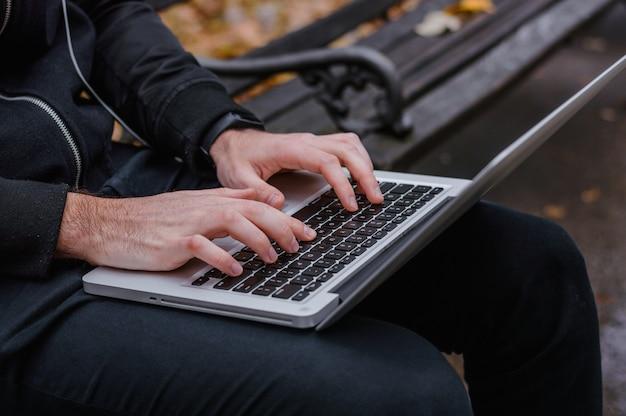 Mãos ocupadas digitando em um laptop no parque Foto Premium