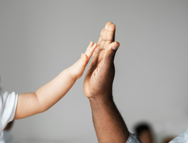 Mãos pequenas e grandes, fazendo um high five Foto gratuita