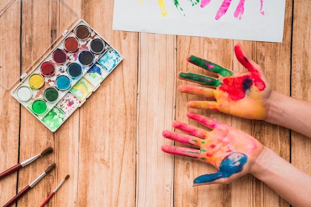 Mãos pintadas com paleta de aquarela; pincéis e papel na mesa de madeira Foto gratuita