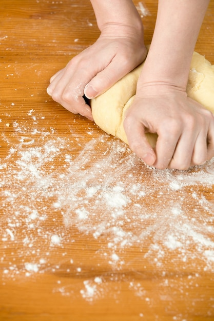 Mãos que amassam a massa de pão Foto gratuita