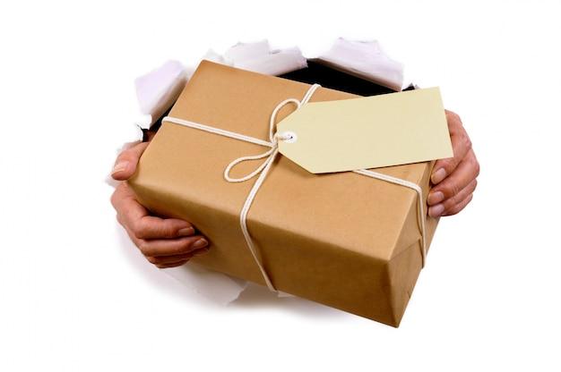 Mãos que entrega o pacote de correio através fundo de papel rasgado branco Foto gratuita