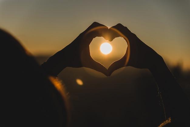 Mãos que fazem a forma de um coração com o sol no meio Foto gratuita