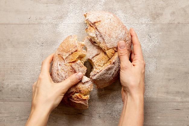 Mãos quebrando um pão delicioso Foto gratuita