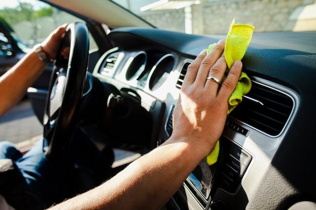 Mãos segurando a roda e polir o interior do carro Foto gratuita