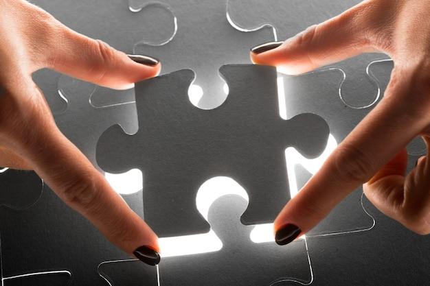 Mãos segurando as peças do puzzle, fundo de conceito de negócio Foto Premium