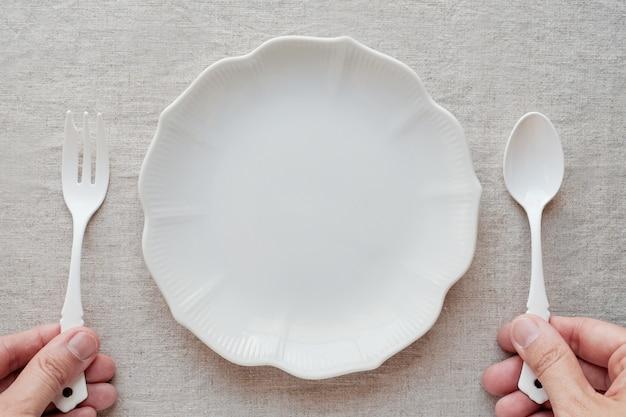 Mãos, segurando, colher garfo, com, prato vazio Foto Premium