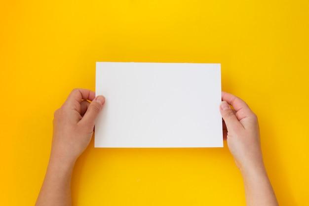 Mãos, segurando, em branco branco, vazio, papel, isolado, ligado, amarela, com, espaço cópia Foto Premium