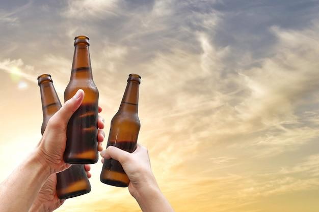 Mãos, segurando, garrafas cerveja, e, feliz, desfrutando, tempo colheita, junto, para, tinindo, óculos, em, partido ao ar livre Foto Premium