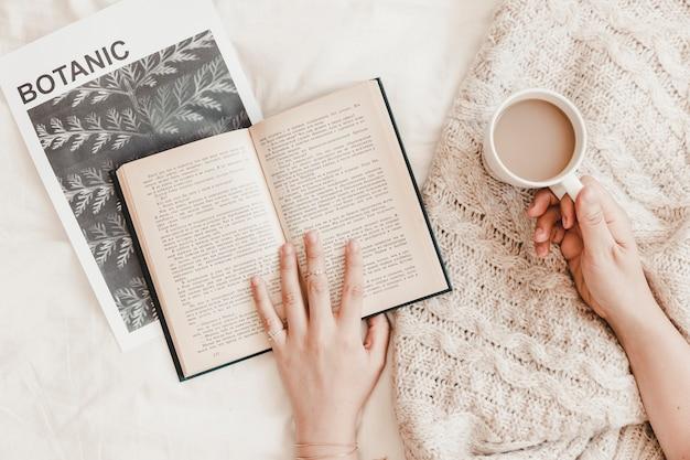 Mãos, segurando, livro, e, bebida quente, mentindo, ligado, cartaz, e, xadrez, ligado, bedsheet Foto gratuita