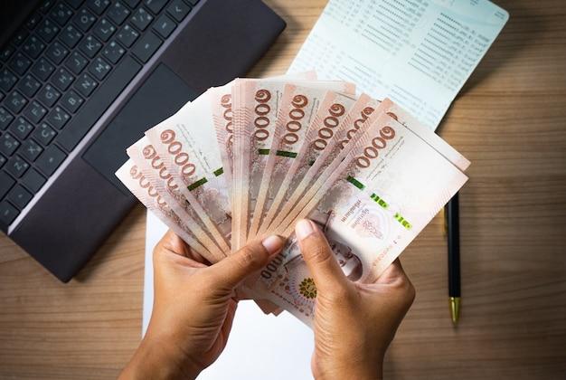Mãos segurando o dinheiro na mesa com o caderno e o livro de conta Foto Premium