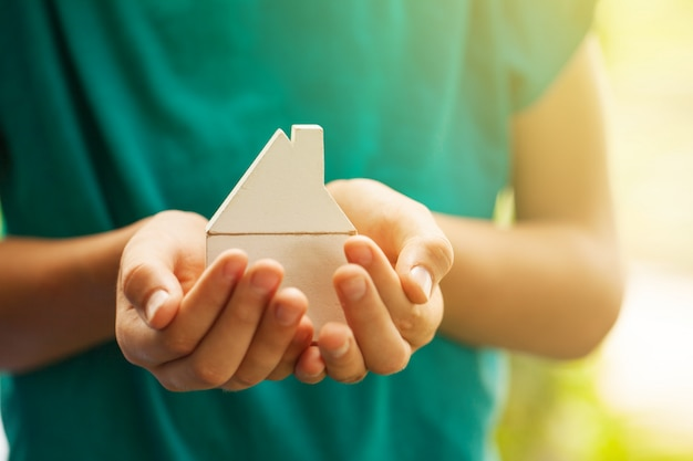 Mãos segurando o modelo de casa de madeira. comprando um novo conceito de seguro de casa e casa. Foto Premium