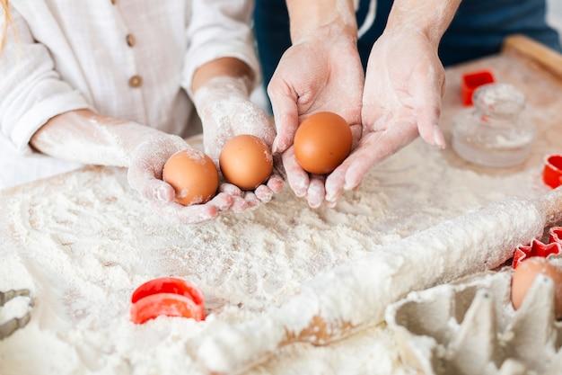 Mãos segurando ovos para fazer massa Foto gratuita