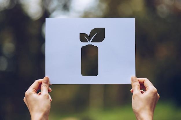 Mãos segurando papel cortado folhas mostrando economia de energia da bateria Foto Premium