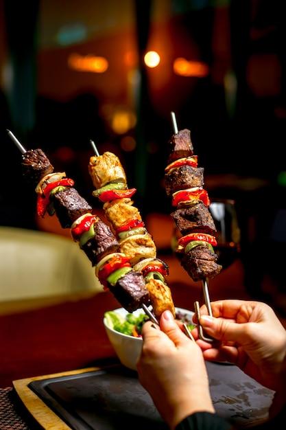 Mãos segurando shish kebab com pimentão colorido Foto gratuita