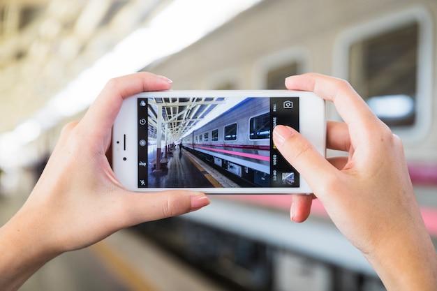 Mãos, segurando, smartphone, ligado, plataforma, perto, trem Foto gratuita