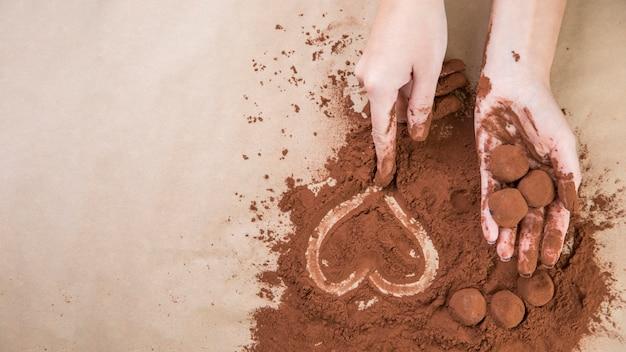 Mãos, segurando, trufas chocolate, com, cacau, pó Foto gratuita