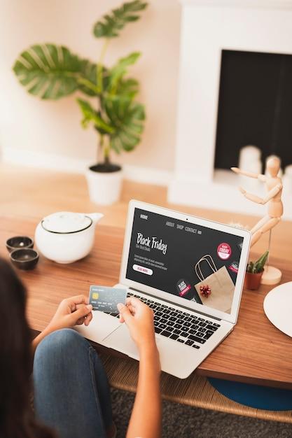 Mãos segurando um cartão de crédito ao lado de um laptop mock up Foto gratuita
