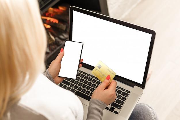 Mãos segurando um cartão de crédito e usando telefone móvel esperto com manhã Foto Premium