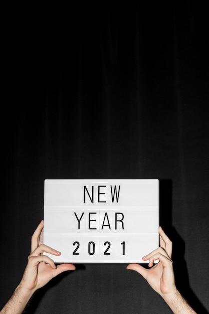 Mãos segurando um cartaz de ano novo de 2021 com espaço de cópia Foto Premium