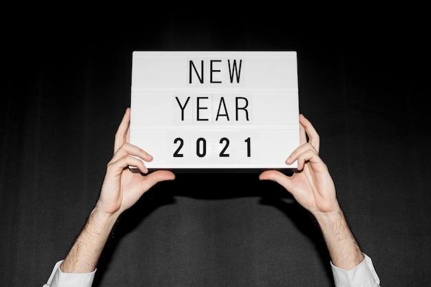 Mãos segurando um cartaz de ano novo de 2021 Foto Premium