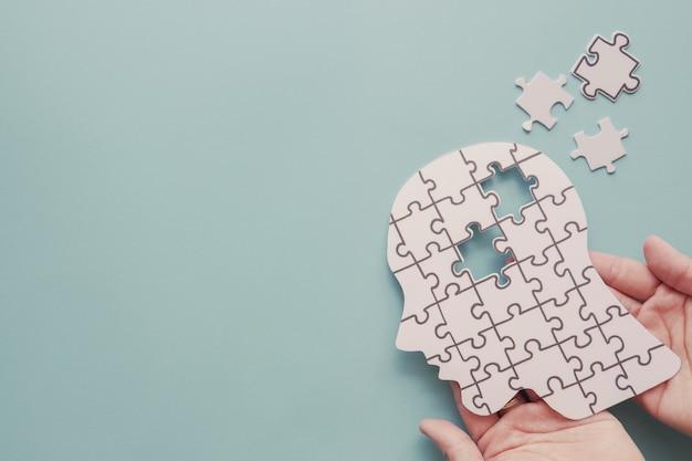 Mãos segurando um cérebro com recorte de papel de quebra-cabeça, dia mundial da saúde mental Foto Premium